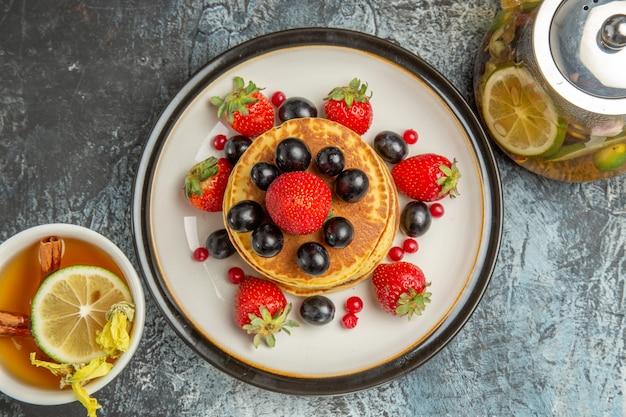 Bovenaanzicht lekkere pannenkoeken met fruit en thee op licht