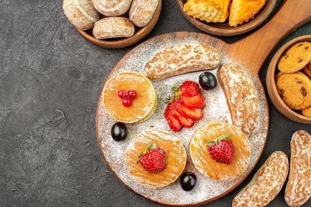 Bovenaanzicht lekkere pannenkoeken met fruit en zoete taarten in het donker