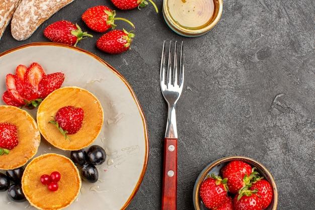 Bovenaanzicht lekkere pannenkoeken met fruit op donker