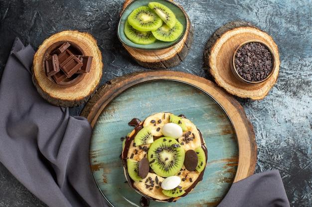 Bovenaanzicht lekkere pannenkoeken met gesneden fruit en chocolade op donkergrijs oppervlak zoete kleur ontbijt suiker cake dessert