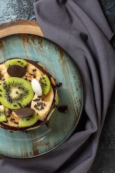 Bovenaanzicht lekkere pannenkoeken met gesneden fruit en chocolade op donkergrijs oppervlak zoete kleur ontbijt suiker fruitcake