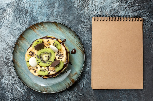 Bovenaanzicht lekkere pannenkoeken met gesneden fruit en chocolade op een donker oppervlak kleur ontbijt suiker fruit zoete cake dessert