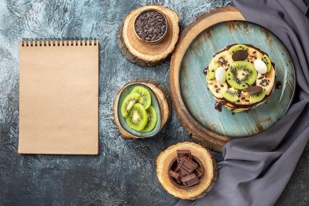Bovenaanzicht lekkere pannenkoeken met gesneden fruit en chocolade op een donkergrijze achtergrond zoete kleur ontbijt suiker fruit cake dessert