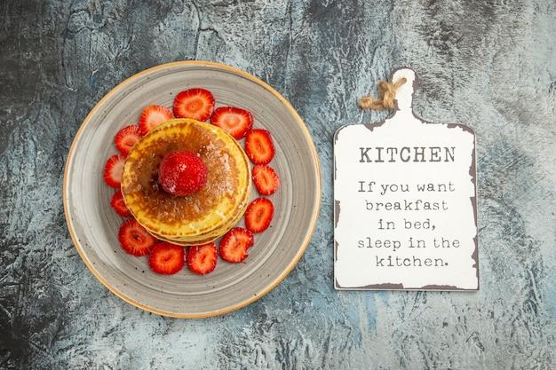 Bovenaanzicht lekkere pannenkoeken met honing en aardbeien op licht