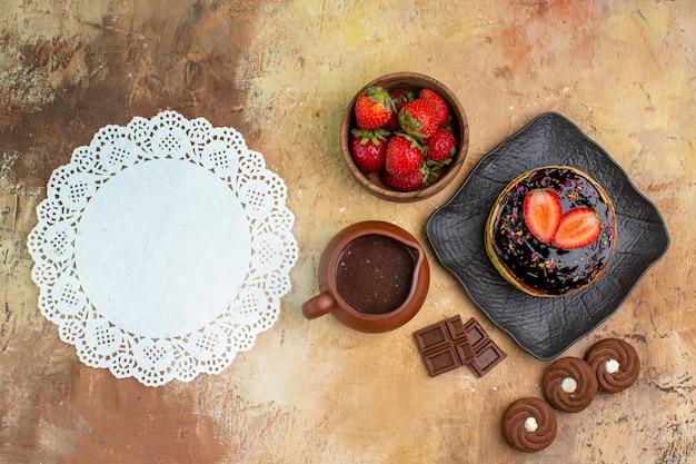 Bovenaanzicht lekkere pannenkoeken met koekjes en fruit op houten bureau