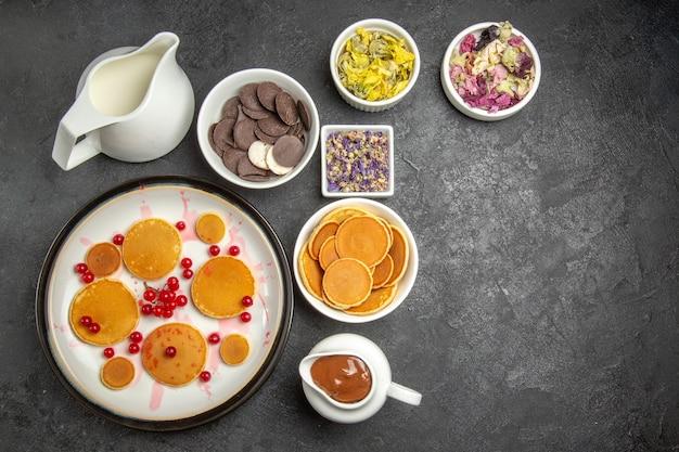 Bovenaanzicht lekkere pannenkoeken met koekjes op donkere achtergrond