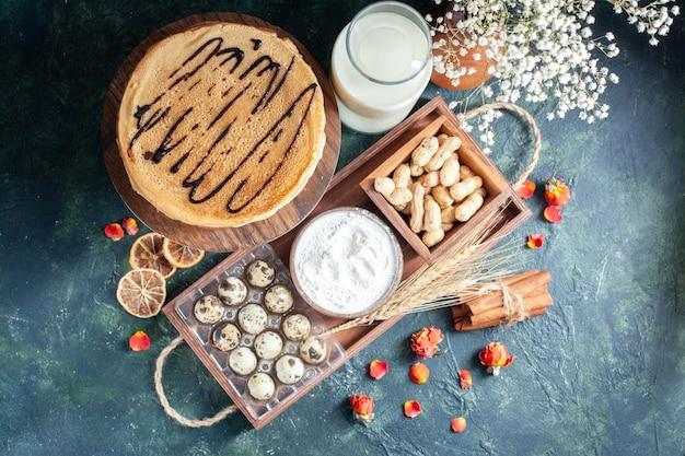 Bovenaanzicht lekkere pannenkoeken met melk en noten op donkerblauwe achtergrond ochtendtaart dessert zoete cake honing ontbijt melk Gratis Foto