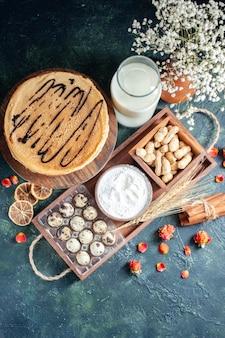 Bovenaanzicht lekkere pannenkoeken met noten en melk op donkerblauwe achtergrond ochtendtaart dessert zoete cake ontbijt melk