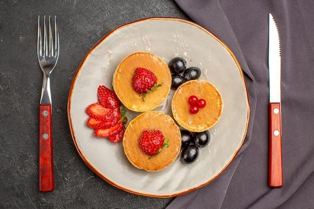 Bovenaanzicht lekkere pannenkoeken met olijf en fruit op donker
