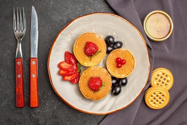 Bovenaanzicht lekkere pannenkoeken met olijven en fruit in het donker