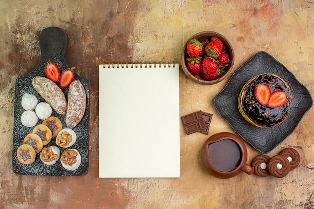 Bovenaanzicht lekkere pannenkoeken met snoep en fruit op houten bureau