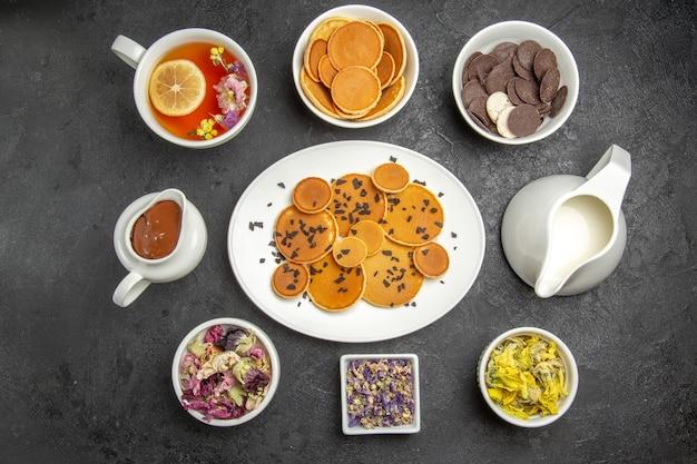 Bovenaanzicht lekkere pannenkoeken met thee en koekjes op de donkere achtergrond