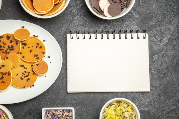 Bovenaanzicht lekkere pannenkoeken met thee en koekjes op donker bureau