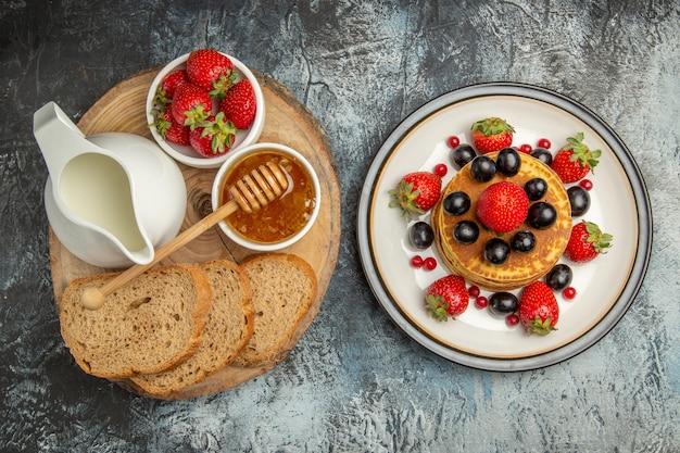 Bovenaanzicht lekkere pannenkoeken met vers fruit en brood op licht
