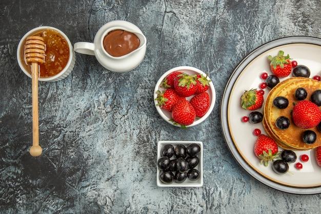 Bovenaanzicht lekkere pannenkoeken met vers fruit en honing op licht