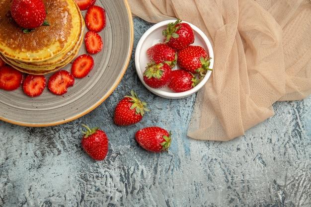 Bovenaanzicht lekkere pannenkoeken met verse aardbeien op licht