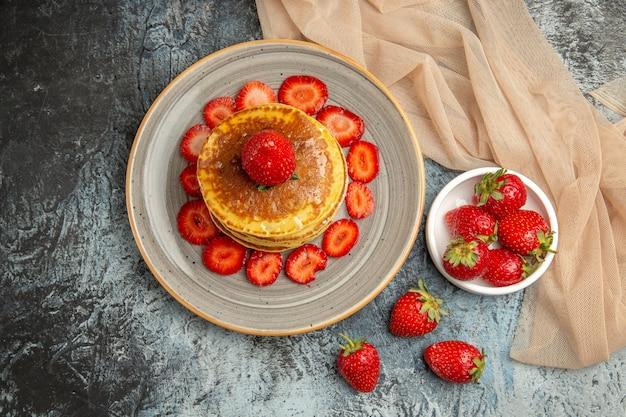 Bovenaanzicht lekkere pannenkoeken met verse aardbeien op lichte vloer