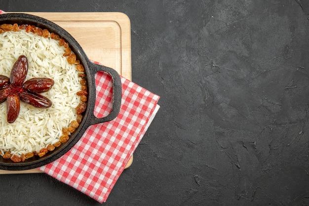 Bovenaanzicht lekkere plov gekookte rijstschotel met rozijnen op de donkere achtergrond rozijnen rijstschotel eten dinerolie