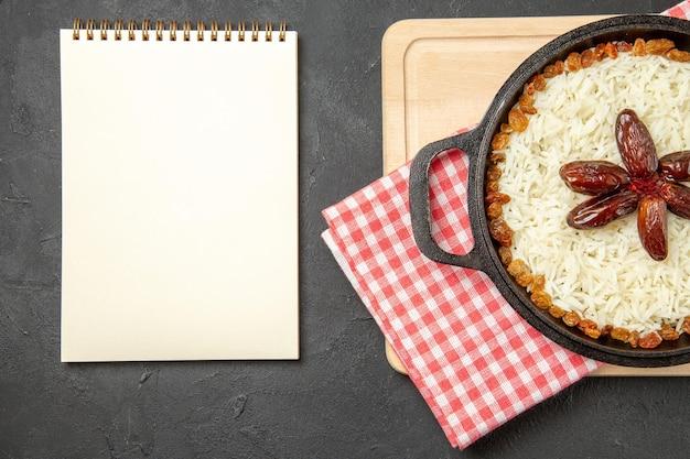 Bovenaanzicht lekkere plov gekookte rijstschotel met rozijnen op donkere bureau rozijnen rijstschotel eten dinerolie