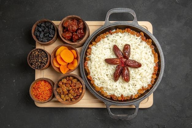 Bovenaanzicht lekkere plov gekookte rijstschotel met verse rozijnen op donkere achtergrond rozijnenschotel rijst diner olie eten