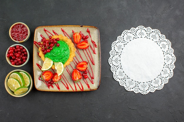 Bovenaanzicht lekkere romige cake met aardbeien op de donkere achtergrond zoete thee suiker dessert