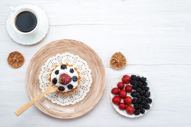 Bovenaanzicht lekkere romige cake met bessen samen met een kopje koffiebessen op de lichte bureaucake met zoete kleurbes