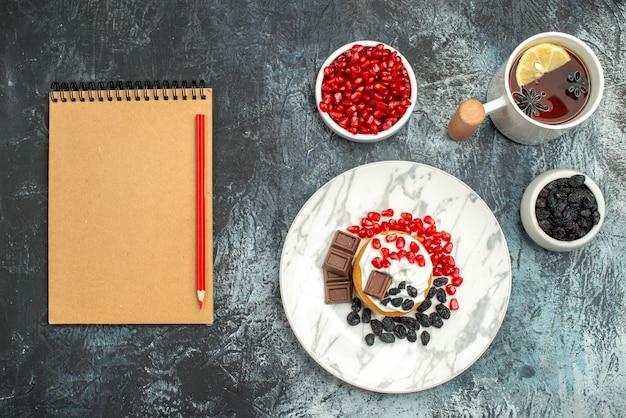 Bovenaanzicht lekkere romige cake met choco koekjes en kopje thee op de licht-donkere achtergrond