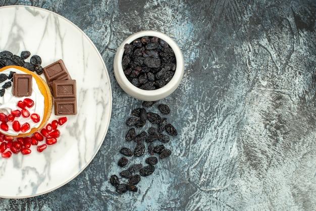 Bovenaanzicht lekkere romige cake met chocolade granaatappels en rozijnen op licht-donkere achtergrond