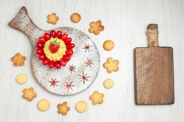 Bovenaanzicht lekkere romige cake met fruit en koekjes op wit bureau
