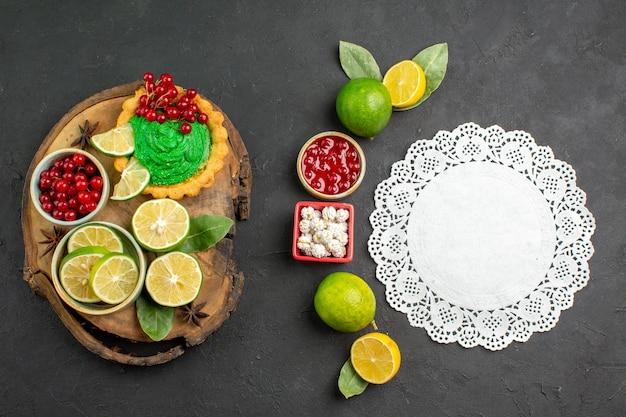 Bovenaanzicht lekkere romige cake met fruit op donkere achtergrond zoete koekjeskoekjes