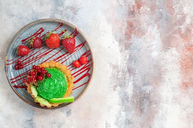 Bovenaanzicht lekkere romige cake met fruit op lichttafel, koekjes dessert zoete cake
