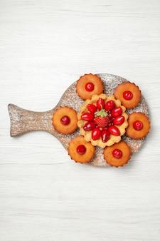 Bovenaanzicht lekkere romige cake met gebak en fruit op wit bureau