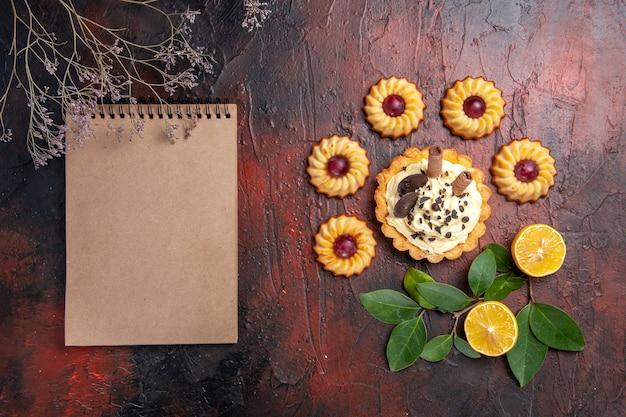 Bovenaanzicht lekkere romige cake met koekjes op de donkere tafel dessert zoete koektaart