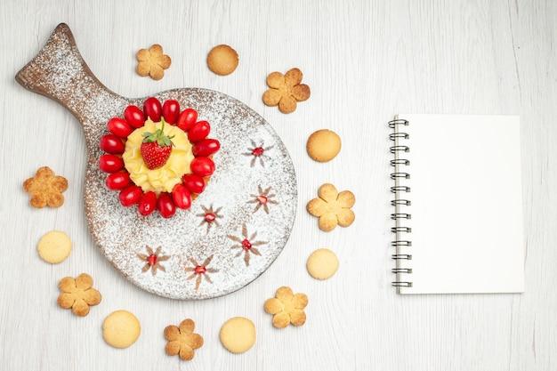 Bovenaanzicht lekkere romige cake met kornoeljes en koekjes op wit bureau