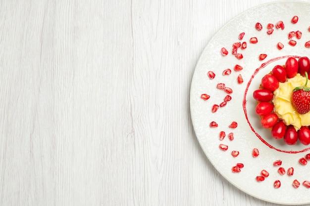 Bovenaanzicht lekkere romige cake met kornoeljes op wit bureau