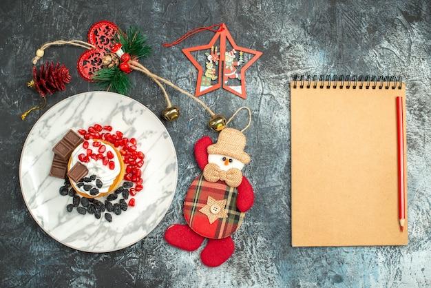 Bovenaanzicht lekkere romige cake met rozijnen en kerstmisspeelgoed op licht-donkere achtergrond