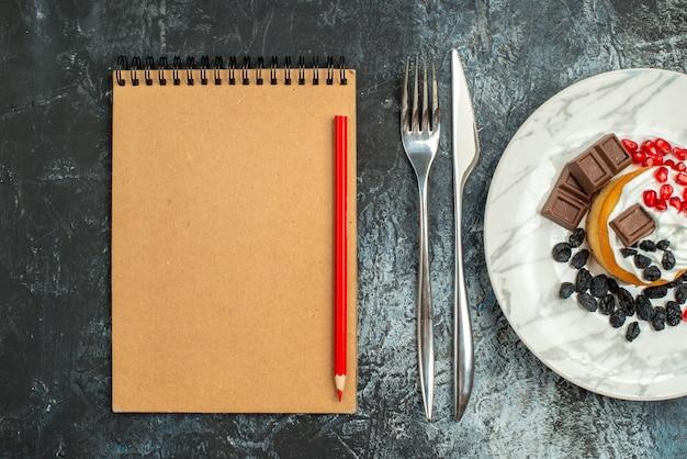 Bovenaanzicht lekkere romige cake met rozijnen en kopje thee op licht-donkere achtergrond
