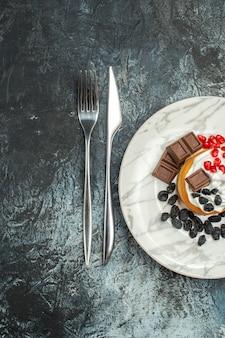Bovenaanzicht lekkere romige cake met rozijnen op licht-donkere achtergrond