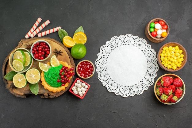 Bovenaanzicht lekkere romige cake met snoep en fruit op het donkere achtergrond zoete koekjeskoekje