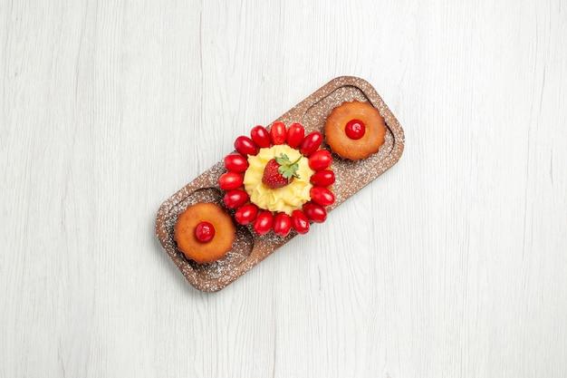 Bovenaanzicht lekkere romige cake met taarten op een wit bureau thee koekje cake koekjes
