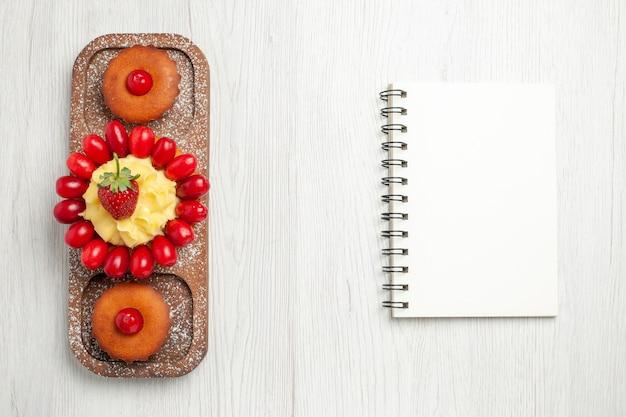 Bovenaanzicht lekkere romige cake met taarten op wit bureau
