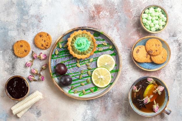 Bovenaanzicht lekkere romige cake met thee op lichte achtergrond zoete foto snoep koekje