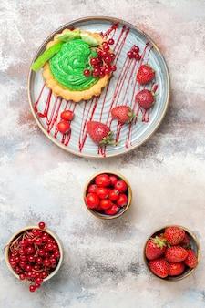 Bovenaanzicht lekkere romige cake met vers fruit op de lichte tafel biscuit dessert cake zoet