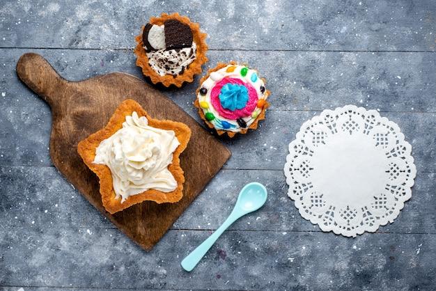 Bovenaanzicht lekkere romige cake stervormig met koektaarten en blauwe lepel op de lichte vloer cake biscuit crème zoete thee