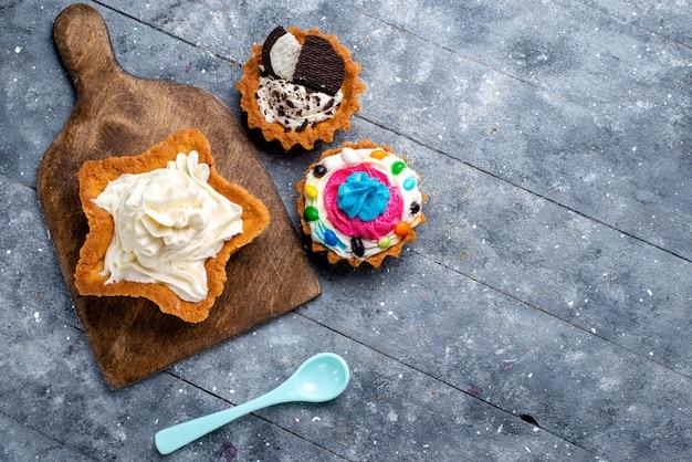 Bovenaanzicht lekkere romige cake stervormig met koektaarten en blauwe lepel op het licht bureau cake biscuit crème zoete thee