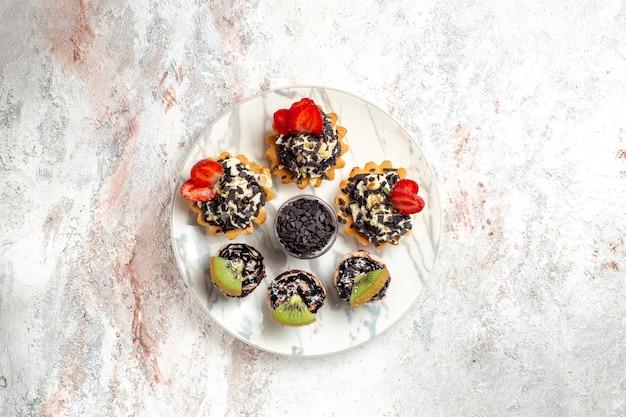 Bovenaanzicht lekkere romige taarten kleine desserts voor thee met fruit en chocoladeschilfers op een wit oppervlak fruitcake cream biscuit pie tea