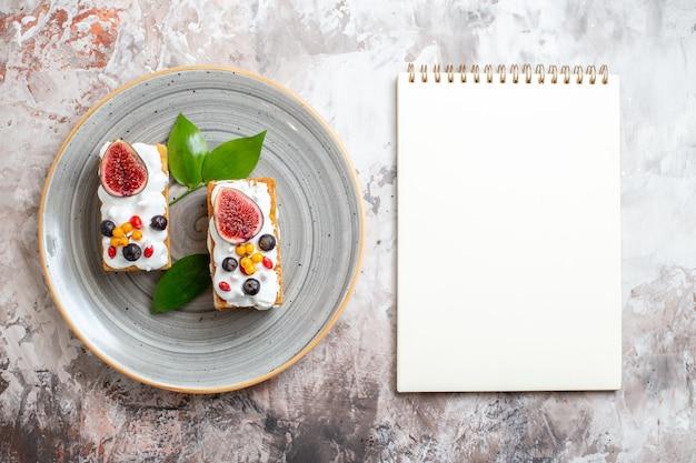 Bovenaanzicht lekkere romige taarten met vers fruit op lichte achtergrond