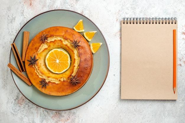 Bovenaanzicht lekkere ronde taart heerlijk dessert voor thee met stukjes sinaasappel op witte achtergrond fruit cake taart biscuit thee zoet dessert