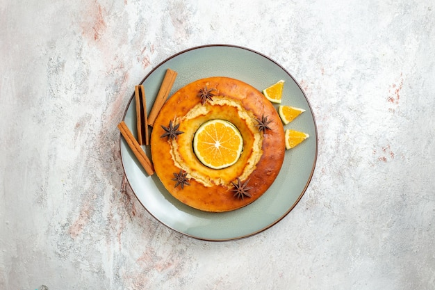 Bovenaanzicht lekkere ronde taart heerlijk dessert voor thee met stukjes sinaasappel op witte achtergrond fruitcake taart biscuit thee zoet dessert