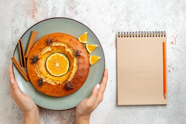Bovenaanzicht lekkere ronde taart heerlijk dessert voor thee met stukjes sinaasappel op witte achtergrond fruitcake taartkoekje zoet dessert Gratis Foto